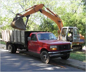 Excavator Loading Debris Into Junk Removal Truck